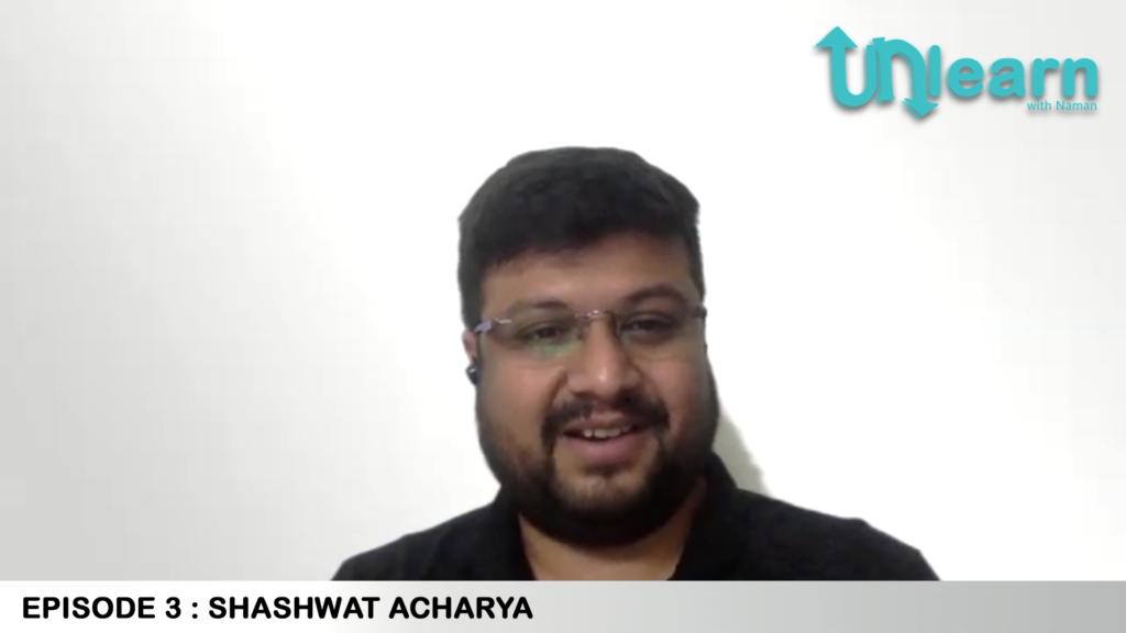 Sashwat Acharya: Young man with short dark hair, glasses, and close-cropped full beard, smiling at camera